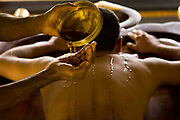 A patient has warm medicated oil poured over his whole body to prepare him for body massage as part of the overall Ayurveda experience at Kalari Kovalikom, Kerala, India.
