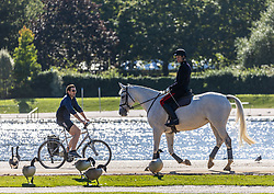 Licensed to London News Pictures. 06/10/2021. London, UK. After yesterday's torrential rains and flooding, An officer exercises his horse in the sunshine in Hyde Park, London today as weather forecasters predict a mild few days ahead with highs of 20c. Photo credit: Alex Lentati/LNP