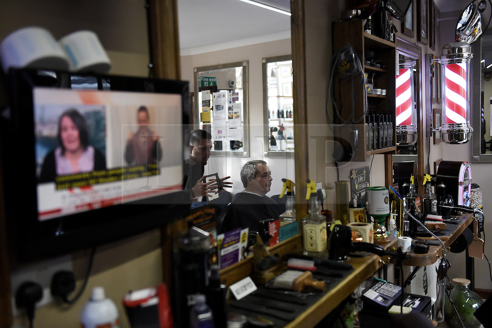 """© London News Pictures. """"Looking for Nigel"""". A body of work by photographer Mary Turner, studying UKIP leader Nigel Farage and his followers throughout the 2015 election campaign. PICTURE SHOWS - Nigel Farage has a haircut at the tradtional Hamilton's Barbers shop in Redruth, Cornwall, as he tours the South West of England on the campaign trail, on March 6th 2015. . Photo credit: Mary Turner/LNP **PLEASE CALL TO ARRANGE FEE** **More images available on request**"""