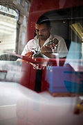 A London bus driver plays a Ukulele, a small guitar, between driving shifts, London, UK
