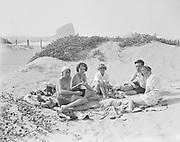 "9969-1556. ""The Gang"" eating lunch at Pacific City beach (Harry Clarke, Betty Ellsworth, Arlethea McDougall, Bill Sisler, and ""Pat"" Morrison). September 2, 1934."