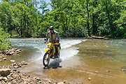 James Pratt crosses the rushing Buffalo River on his Suzuki DRZ400S motorcycle after a recent rain.