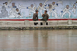 © Licensed to London News Pictures. 12/08/2011. Sariwon, North Korea. Two North Korean soldiers rest next to a pond in the town of Sariwon. North Korea has one of the largest standing armies in the world with over 1,100,000 soldiers on active duty. Photo credit : James Gourley/LNP/