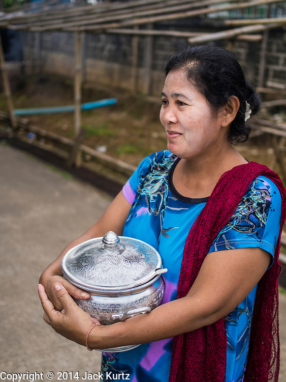 16 SEPTEMBER 2014 - SANGKHLA BURI, KANCHANABURI, THAILAND:  A woman waits to make merit and present Mon Buddhist monks with food during the morning alms round in the Mon community in Sangkhla Buri. The Mon were some of the first people to settle in Southeast Asia, and were responsible for the spread of Theravada Buddhism in Thailand and  Indochina. The Mon homeland is in southwestern Thailand and southeastern Myanmar (Burma). The Mon in Thailand traditionally allied themselves with the Thais during the frequent wars between Burmese and Siamese Empires in the 16th - 19th centuries and the Mon in Thailand have been assimilated into Thai culture. The Mon in Myanmar were persecuted by the Burmese government and many fled to Thailand. Sangkhla Buri is the center of Burmese Mon culture in Thailand because thousands of Mon came to this part of Thailand during the persecution.   PHOTO BY JACK KURTZ