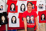 01 JULY 2011 - BANGKOK, THAILAND:     A woman sells Yingluck Shinawatra tee shirts before a Pheua Thai election rally in Bangkok Friday. Yingluck is the Pheua Thai candidate for Thai Prime Minister. Thailand's divisive election campaign drew to a close Friday in Bangkok. Most of the parties had large rallies in an effort to sway last minute undecided voters. Pheua Thai, the party of ousted Prime Minister Thaksin Shinawatra held a massive rally in Rajamakala Stadium (also called Ramkamhaeng Stadium) to close out their campaign. A monsoon thunderstorm didn't keep people away from the event. Most Thai public opinion polls show Pheua Thai with a healthy lead over their arch rivals (and incumbent party in power) the Democrats. Thaksin's youngest sister, Yingluck Shinawatra, is running for Prime Minister under the Pheua Thai banner. If elected, she will be Thailand's first female Prime Minister.   PHOTO BY JACK KURTZ