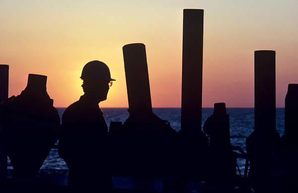 Offshore oil rig worker in hard hat silhouetted at sunset.