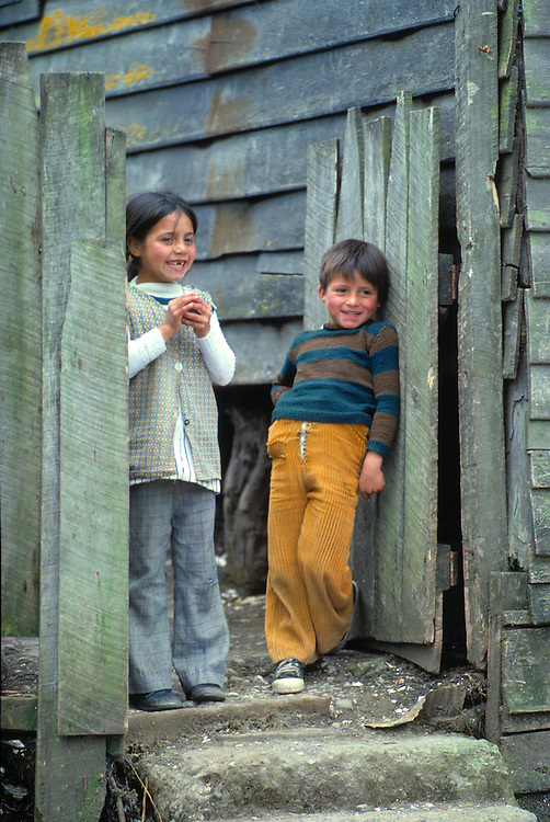 Smiling children pose in the gateway of their home in Calbulco near Puerto Montt in Chile.