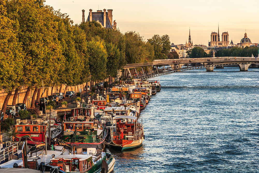 Boats are moored on the quays in the heart of Paris, France. Living on a houseboat in Paris is a romantic notion and an alternative to a hotel.