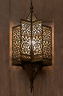 Lit, Moroccan, Arabian lamp with intricate decor hanging on wall. Concept for Moroccan and Arabian culture and design.