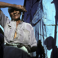 Haiti, Port-au-Prince, Woman shades eyes at sunrise in Cite Soleil slum along city's coastline