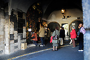 """People praying at a shrine containing a relic painting of the Virgin Mary, at the 13th century Stone Gate (Kamenita vrata). Plaques of """"Hvala"""" (""""thank you"""") to the Virgin are attached to the wall at the left. Zagreb, Croatia"""