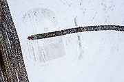Drone photo of a farmer working his land after a fresh snowfall.