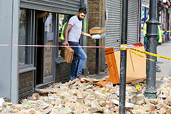 © Licensed to London News Pictures. 10/03/2019. London, UK. A man from Stokey Vintage Cafe on Stoke Newington High Street collects his belonging outside the cafe after the roof collapsed this morning due to high winds. Photo credit: Dinendra Haria/LNP
