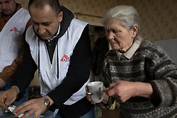 Doctor Kachatur Malakyan (r) and nurse Andrei Bogma of MSF provide home visits to Valentina, 76, and Nikolai, 77,Shevchuck in their home in Debalseve. Nikola suffers from chronic cardia disease and is bed-ridden. He relies on his wife to take care of him. MSF provides vital home care to patients like Nikolai who are house-bound and have stopped receiving medical care in the embattled eastern Ukranian town.
