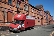 Old work van parked outside a red brick factory building on Haden Street in Balsall Heath, Birmingham, United Kingdom. Birmingham has a thriving industrial present and past with many bussinesses still operating from their original premises.