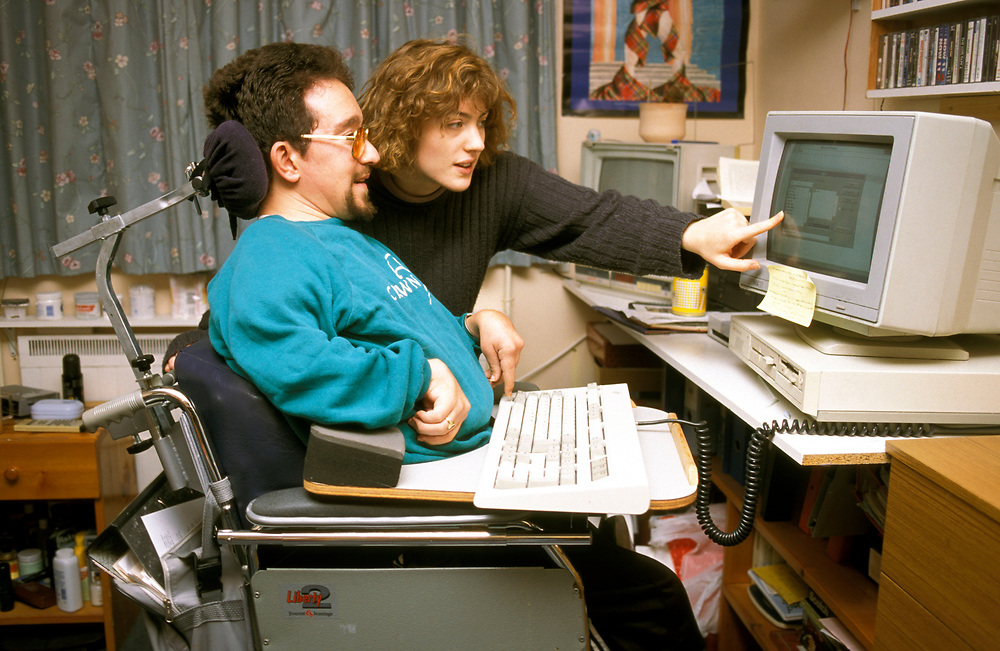 Disabled man working on his computer in residential home.
