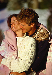 Couple outdoors in sweaters and blanket in each other's arms