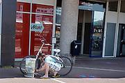 In Utrecht pompt een jongen de banden van zijn fiets op met een zogenaamde DUCO fietspompzuil. De zuilen worden aangeboden door de Utrechtse ondernemer Duco Douwstra om fietsers de mogelijkheid te geven overal hun banden op te pompen. De zuil is uit beton gegoten, zodat het niet zomaar meegenomen kan worden.<br /> <br /> In Utrecht a man pumps the tires of his bike with a bicycle pump called DUCO column. The columns are offered by the Utrecht entrepreneur Duco Douwstra in order to allow every cyclists anywhere to pump their ties.  The column is cast from concrete, so that it can not be simply taken into account.