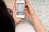 A woman using an iPhone4s. This image may contain copyrighted elements. Please contact Apple for permission to use for commercial usages.