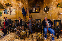 Men smoking sheesha (water pipe) in a cafe in the Arab Souk in the Old City, Jerusalem, Israel.