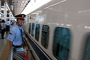 A platform guard blows a whistle an watches a shinkansen bullet train leave Shin Yokohama station, Yokohama, Japan. August 14th 2008