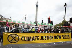 London, UK. 7 October, 2019. Climate activists from Extinction Rebellion use a banner to block Trafalgar Square on the first day of International Rebellion protests to demand a government declaration of a climate and ecological emergency, a commitment to halting biodiversity loss and net zero carbon emissions by 2025 and for the government to create and be led by the decisions of a Citizens' Assembly on climate and ecological justice.