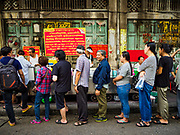 """18 MAY 2017 - BANGKOK, THAILAND: Customers stand in line fresh curries at Jek Pui curry stand, one of the most popular street food stalls in Bangkok. City officials in Bangkok have taken steps to rein in street food vendors. The steps were originally reported as a """"ban"""" on street food, but after an uproar in local and international news outlets, city officials said street food vendors wouldn't be banned but would be regulated, undergo health inspections and be restricted to certain hours on major streets. On Yaowarat Road, in the heart of Bangkok's touristy Chinatown, the city has closed some traffic lanes to facilitate the vendors. But in other parts of the city, the vendors have been moved off of major streets and sidewalks.      PHOTO BY JACK KURTZ"""