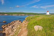 Lighthouse and rocky coastline along the Cabot Strait. Cabot Trail. Cape Breton Island. Appalachian Mountain chain.  <br />Neils Harbour<br />Nova Scotia<br />Canada