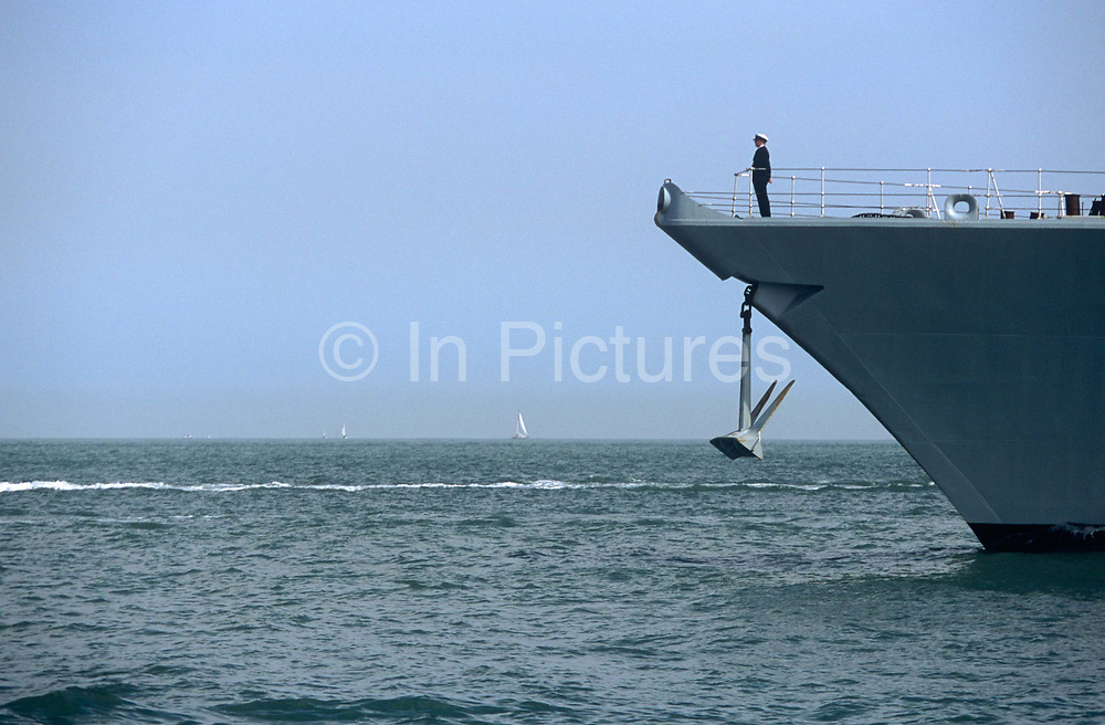 An officer of the Royal Navy looks proudly out to sea while standing at the bow of the frigate HMS Monmouth F235, on 23rd August 2001, near Portsmouth, England.