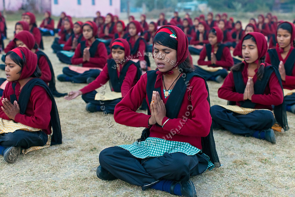 Ritu Gaur, 13, (centre) is praying in the early hours of the morning with other pupils in front of the Jamoniya Tank Girls Hostel, near Sehore, Madhya Pradesh, India, where the Unicef India Sport For Development Project has started in 2012. Covering 313 state-run girls' hostels and 207 mixed hostels in Madhya Pradesh, the project ensures that children from Scheduled Tribes (ST) and others amongst the poorest people in India, can easily access education and be introduced to sports. Field workers from Unicef also oversee their nutrition and monitor the overall conditions of each pupil.