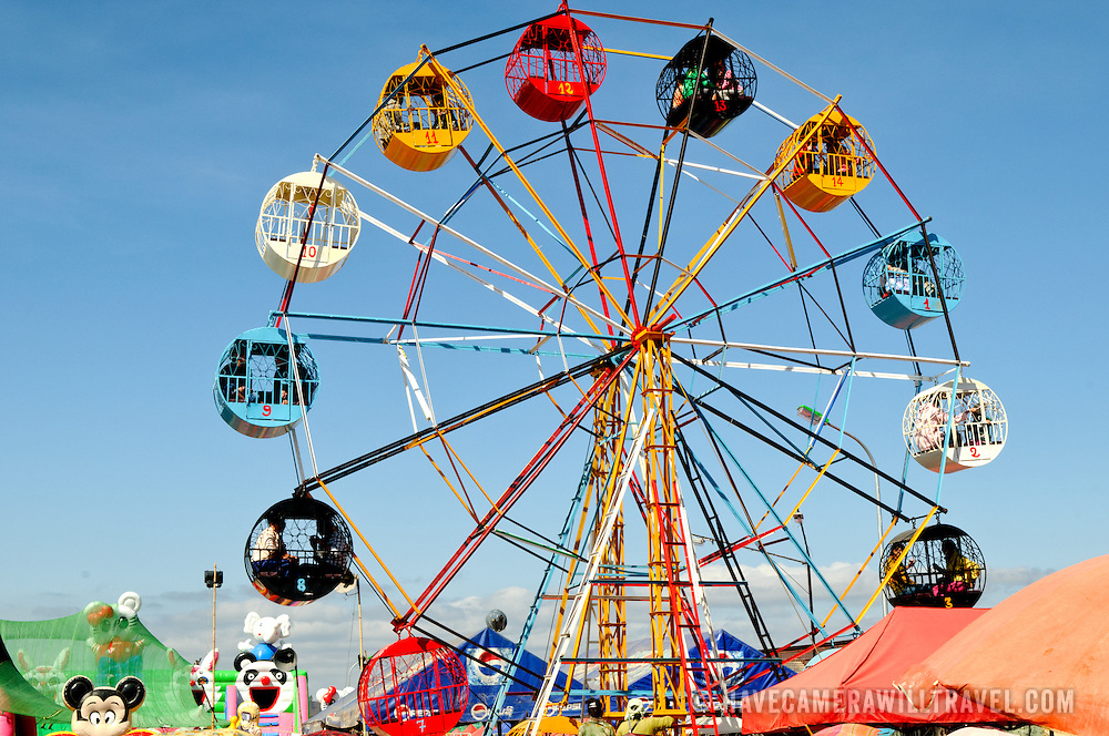 A ferris wheel at the New Year celebration in Phonsavan. Young Hmong men and women flock to the New Year festival in in Phonsavan in northeastern Laos. Hmong girls dress in brightly colored costumes and engage ball games of catch as part of a ritual traditionally designed to find husbands. The people of the region are predominantly of Hmong ethnicity.