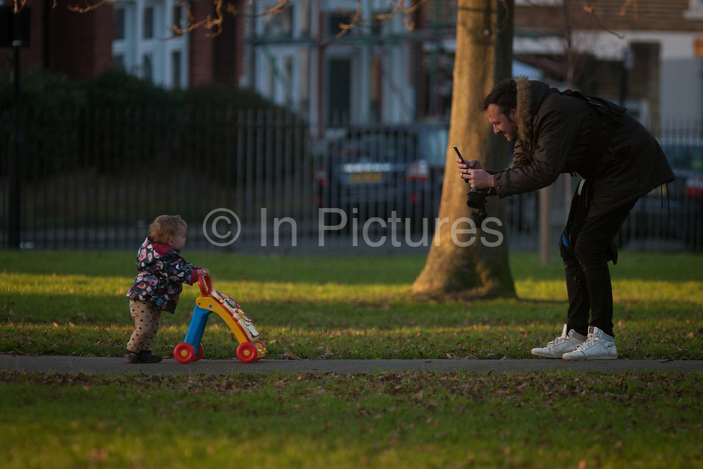 A man uses his smartphone to take a photo of a child pushing a walking trolley, on 5th January 2017, in Ruskin Park, London borough of Lambeth, England.