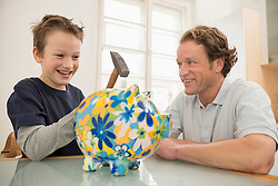 Father and son with piggy bank and hammer