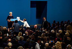 © Licensed to London News Pictures. 04/10/2017. Manchester, UK. British prime minister THERESA MAY being handed a fake P45 form by a protestor, watched over by BORIS JOHNSON (pictured right) during leaders speech on the final day of the Conservative Party Conference. The four day event is expected to focus heavily on Brexit, with the British prime minister hoping to dampen rumours of a leadership challenge. Photo credit: Ben Cawthra/LNP
