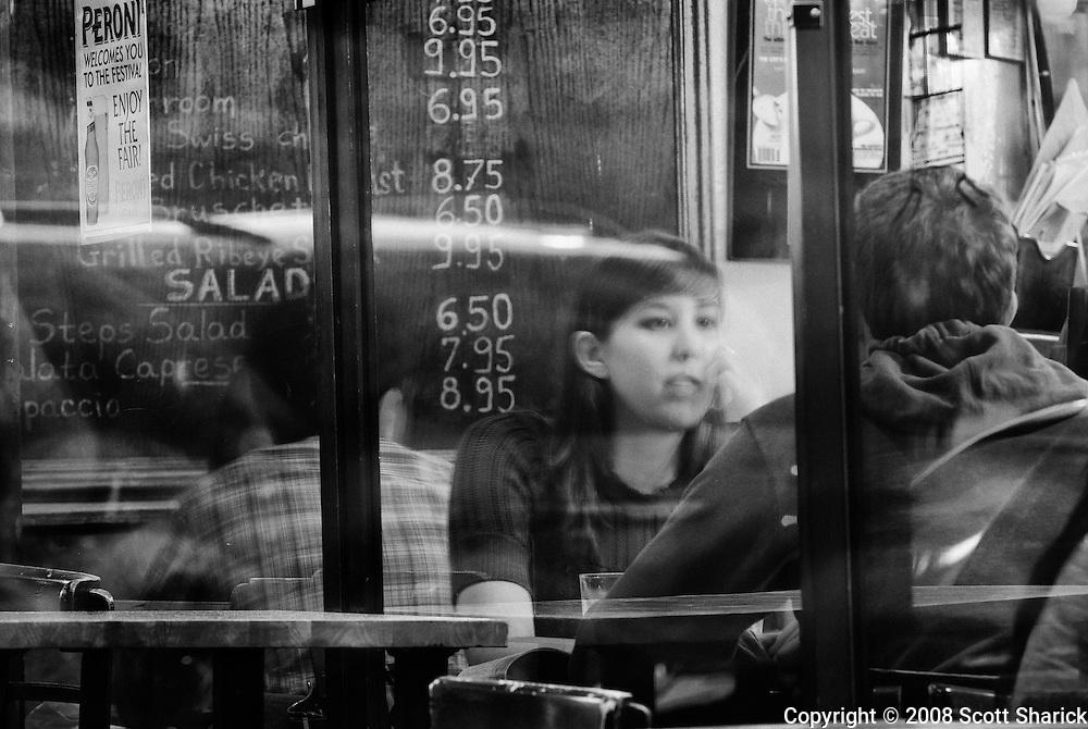 A couple is seen talking through a restaurant window in San Francisco, California.