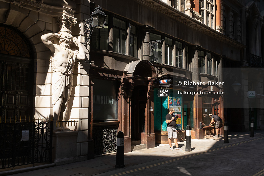 Two workmen stand near the Atlantes figure by the sculptor H.A. Pegram (1896) at the entrance of Drapers' Hall livery company in Throgmorton Street, a gatekeeper stoops to pick up dropped keys outside Drapers Hall in Throgmorton Street, in the City of London, the capital's financial district aka the Square Mile, on 30th July 2020, in London, England. The Drapers' Company is a Livery Company in the City of London whose roots go back to the 13th century, when as its name indicates, it was involved in the drapery trade. While it is no longer involved in the trade, the Company has evolved acquiring a new relevance. Its main role today is to be the trustee of the charitable trusts that have been left in its care over the centuries. The Company also manages a thriving hospitality business. The first Drapers' Hall was built in the 15th century in St Swithin's Lane. It bought a Hall on the present site in Throgmorton Street in 1543 from King Henry VIII for £1,200 (about £350,000 in today's money). The Hall that the Company purchased from King Henry VIII in 1543 had been the private residence of Thomas Cromwell, Earl of Essex until his execution in 1540, when it was confiscated by the Crown.