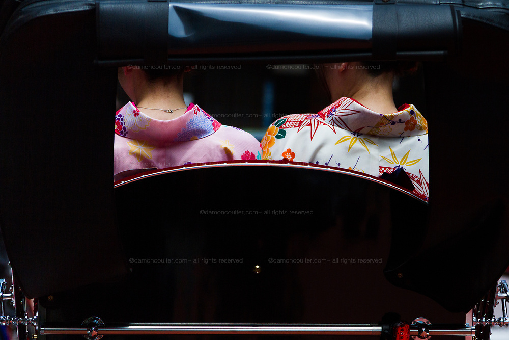 Two Asian tourists wearing Japanese kimono sit in a rickshaw for a tour of Asakusa, Tokyo, Japan. Friday May 18th 2018.