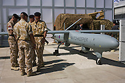 """British Army soldiers gather outside the hospitality chalet of aerospace manufacturer Thales. Standing in mid-day sun, the troops are dressed in ISAF desert uniform, alongside a company-built Watchkkeper an unmanned aerial vehicle (UAV). Watchkeeper WK450 is a £800 million contract awarded in July 2005 to Thales to provide the British Army with  or all weather, Intelligence, Surveillance, Target Acquisition and Reconnaissance (ISTAR) use. It has a weight of 450 kg and a payload capacity of 150 kg, and will have a typical endurance of 17 hours. The MoD's newest and most sophisticated surveillance and targeting drone, the Watchkeeper, is undergoing trials at Aberporth in west Wales. While the arguments over America's policy of """"assassination by drone"""" rage across Pakistan and Afghanistan, fuelling public concern over the cold-eyed automation of warfare, the future of UAVs is quietly taking shape here on the Welsh coast, where there is daily proof that UAVs and manned aircraft can co-exist in British airspace."""