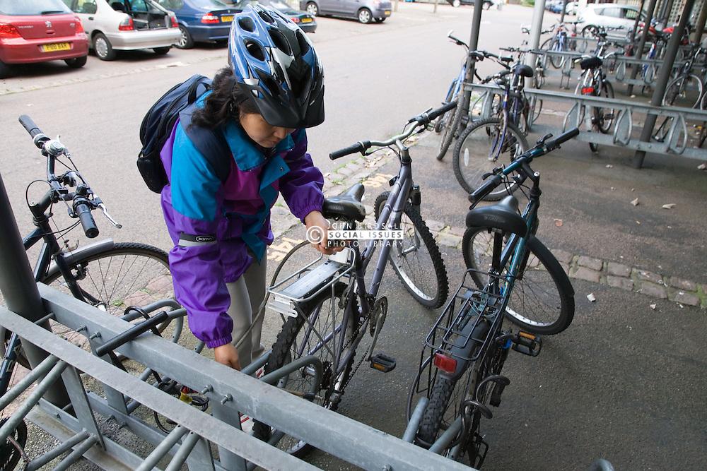 Woman locking up her bike in a works bike shed,