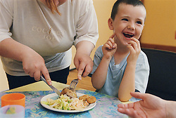 Young boy having lunch with mother helping to cut food,