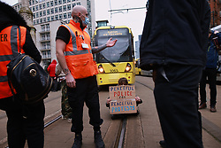 """© Licensed to London News Pictures. 27/03/2021. Manchester, UK. Protesters block trams in St Peter's Square . Hundreds at """" Kill the Bill """" and Reclaim the Streets demonstrations in Manchester City Centre, in opposition to the Police, Crime, Sentencing and Courts Bill 2021 that is currently before Parliament and after the death of Sarah Everard in London . Photo credit: Joel Goodman/LNP"""
