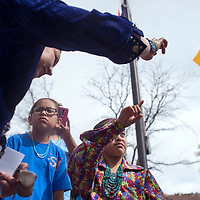 Navajo Nation Council Delegate Amber Crotty, left, gives Jasmine Miller some corn pollen from her personal pouch and walks her through the blessing by pointing east outside theCouncil Chambers in Window Rock Monday. Miller, whose older brother Samuel Miller, right, is Autistic was visiting the council to be honored for her work raising Autism awareness.