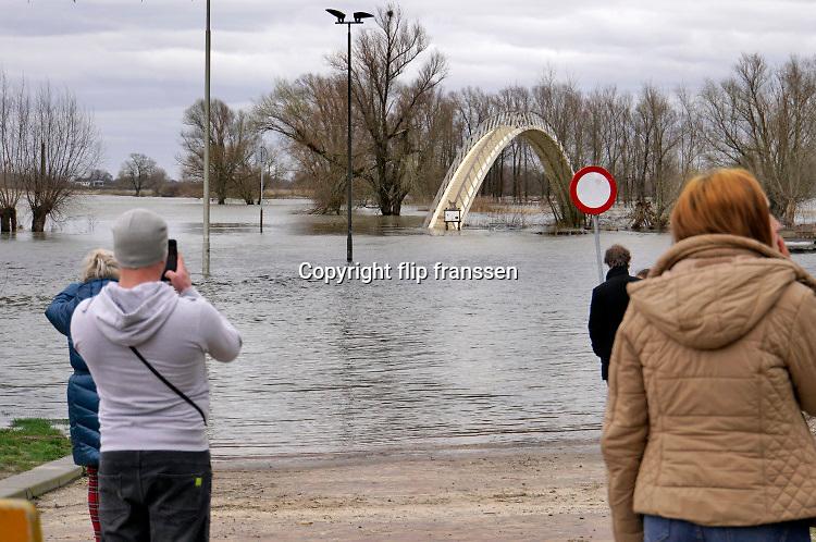 Nederland, Nijmegen, 15-3-2020 Dit weekend was er een kleine hoogwaterpiek. In Nijmegen en de aangrenzende Ooijpolder gingen veel dagjesmensen een wandeling maken langs het water . De voetgangersbrug naar de stadswaard trekt altijd veel bijkijks en wordt veelvuldig gefotografeerd . Foto: Flip Franssen