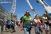 Summertime in London, England, UK. Tourists on the South Bank pass underneath the London Eye on a summers day.