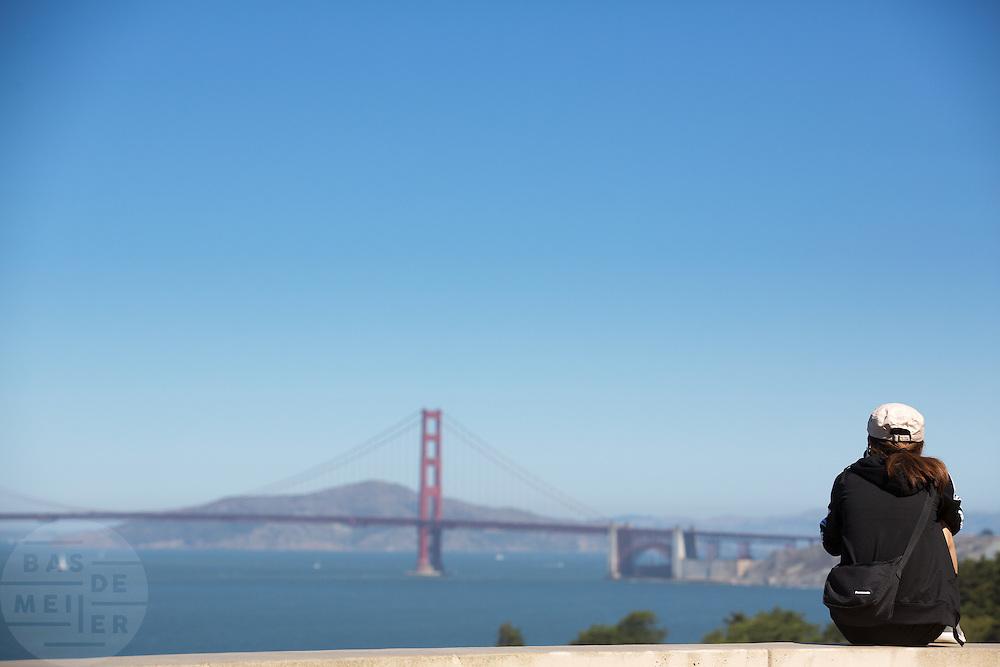 Een vrouw kijkt bij Lands End naar de Golden Gate Brug. Tussen het Schiereiland van San Francisco en Marin County ten noorden van de metropool San Francisco ligt de Golden Gate Brug over de zeestraat Golden Gate, tussen de San Fransisco Bay en de Stille Oceaan. De brug is een van de zeven moderne wereldwonderen en is op 27 mei 1937 geopend. De tolbrug is een van de meest herkenbare symbolen van San Francisco en Californie.<br /> <br /> Between the San Francisco Peninsula and Marin County north of the metropolis of San Francisco's lays Golden Gate Bridge on the Golden Gate strait, between San Francisco Bay and the Pacific Ocean. Lies The bridge is one of the seven modern wonders of the world and was opened on May 27, 1937. The toll bridge is one of the most recognizable symbols of San Francisco and California