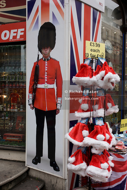 Tacky Christmas tourist trinkets with santa hat and grenadier soldier thems on sale outside a discount shop in New Oxford Street in central London.