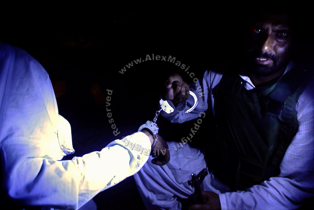A kidnap suspect (left) is being detained for questioning by a member of the AVCC, (Anti-Violence Crime Cell) a special police unit mostly involved in anti-terrorism operations and kidnap cases in the city of Karachi, Pakistan's main economic hub.