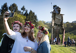 © Licensed to London News Pictures. 05/05/2018. Chalton, UK. Visitors to the Beltain Festival at Butser Ancient Farm take a selfie with the 30 foot high Wickerman figure in Hampshire. Over two thousand people have gathered to witness the ancient Beltain Celtic celebration of summer - which culminates in the burning of the giant Wickerman.  Photo credit: Peter Macdiarmid/LNP