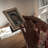"""Renza Volpini holding the framed photo of her daughter in her house in Canneto sull'Oglio. That afternoon she said to me, while she looked at the photo: """"I decided I wanted to be useful to other women. I started to follow the initiatives of other mothers of femicide victims, by taking part in protests and demonstrations. I help other victims of violence who come to me for advice, I try to reassure them on the phone and, if they want, I accompany them to domestic violence support centers."""""""
