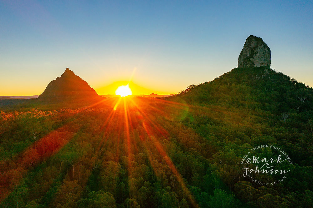 Aerial view of the setting sun behind Mt Beerwah & Mt Coonowrin, Glass House Mountains, Sunshine Coast Hinterland, Queensland, Australia